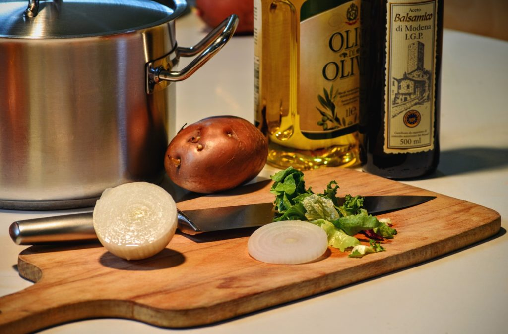 Cutting board with onion and potato. Olive oil bottles in the background.