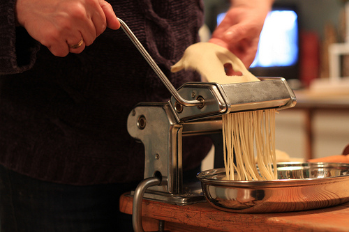 person making pasta using a pasta maker