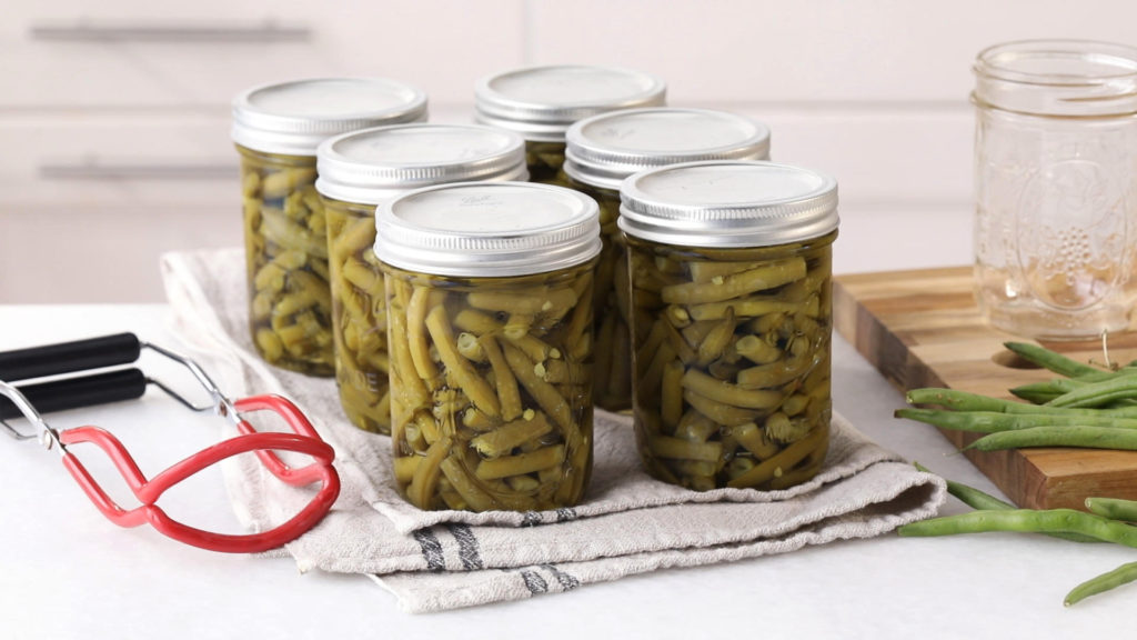 six canning jars filled with green beans cooling on a kitchen towel after being processed