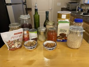 Various pantry items arranged on wooden work surface in a kitchen. (Nuts, cans, grains, dried fruit, etc.)