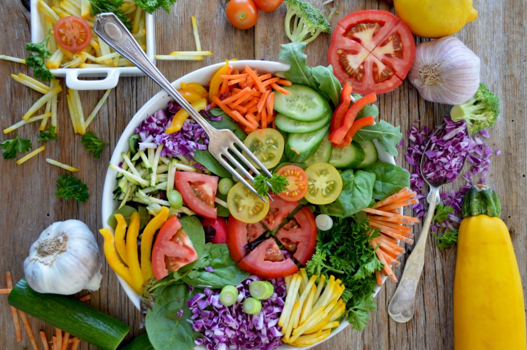 Plate bowl with a variety of vegetables in and around the bowl.