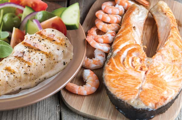 Cooked chicken breast, shrimp, and salmon on a plate and wooden slab.