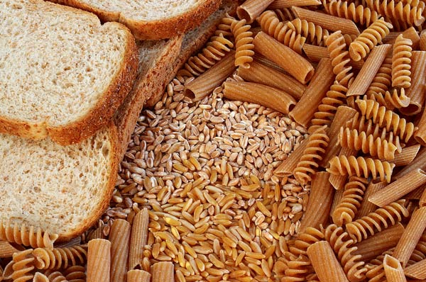 Pile of brown rice and other grain with whole wheat bread and pasta spread around the border of the pile.