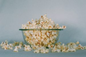 Popcorn in a glass bowl spilling out onto a counter