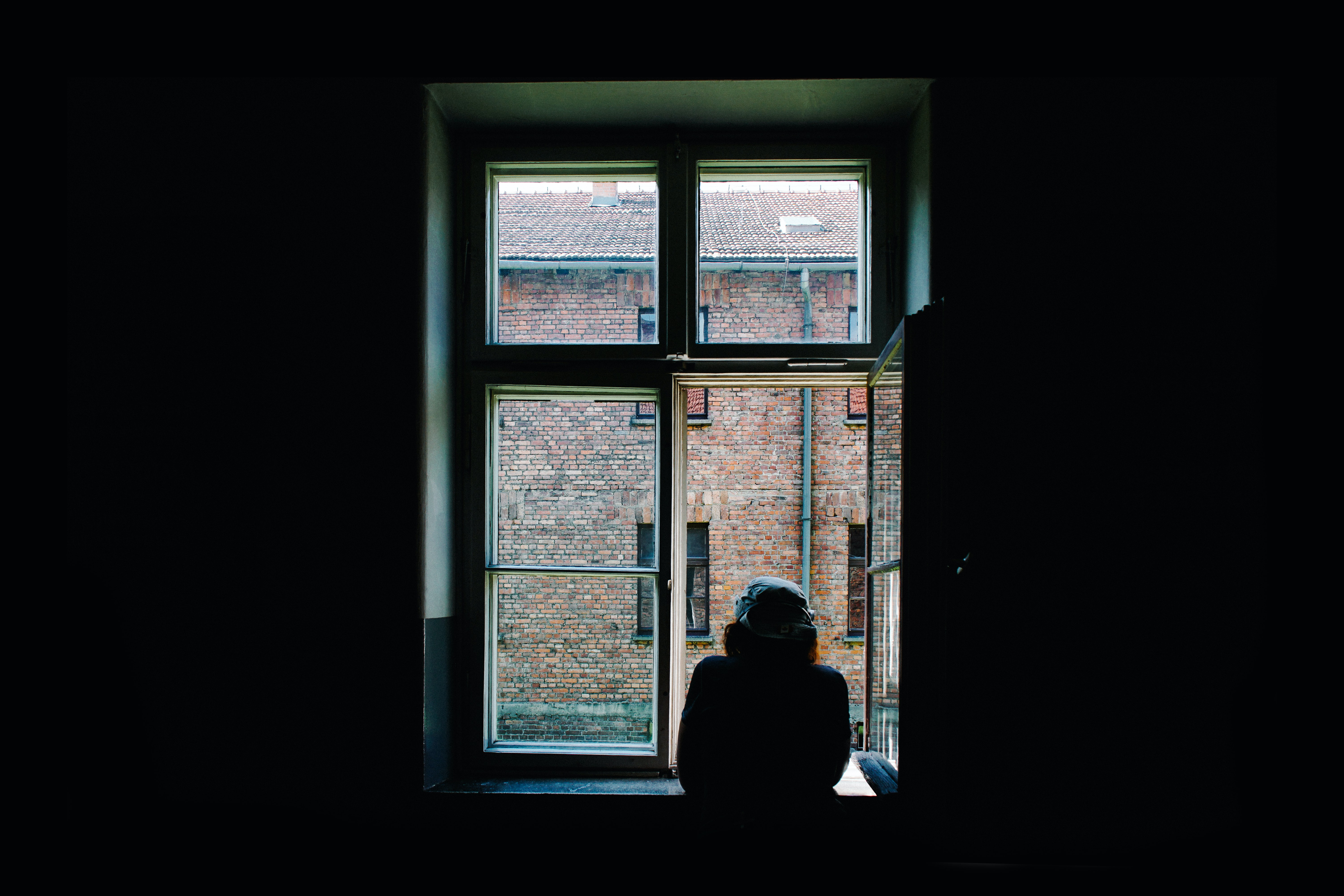 person looking out a window in a dark room