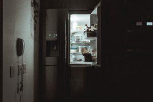 Open refrigerator door in a dark kitchen