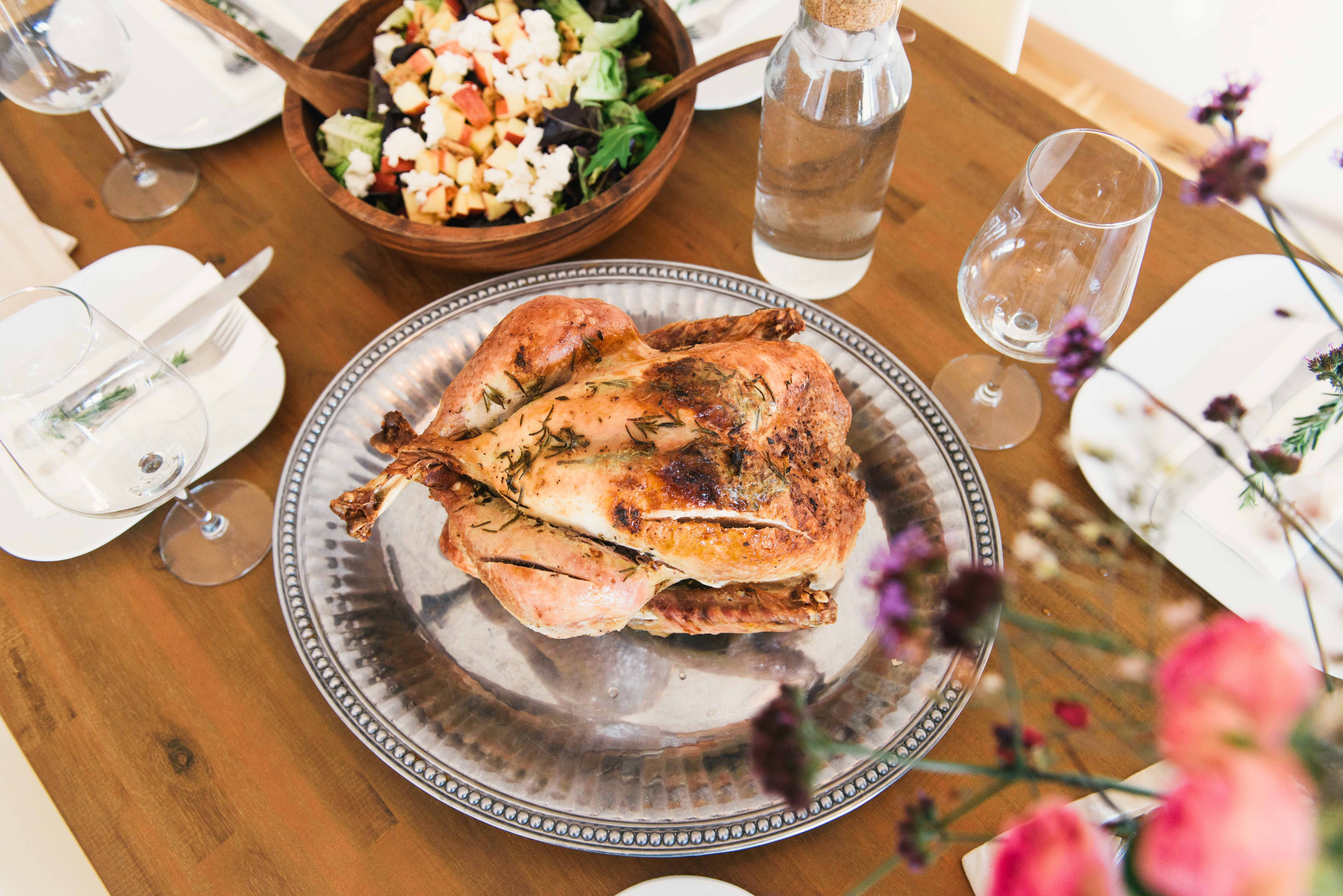 image of a holiday table with a roasted chicken and salad