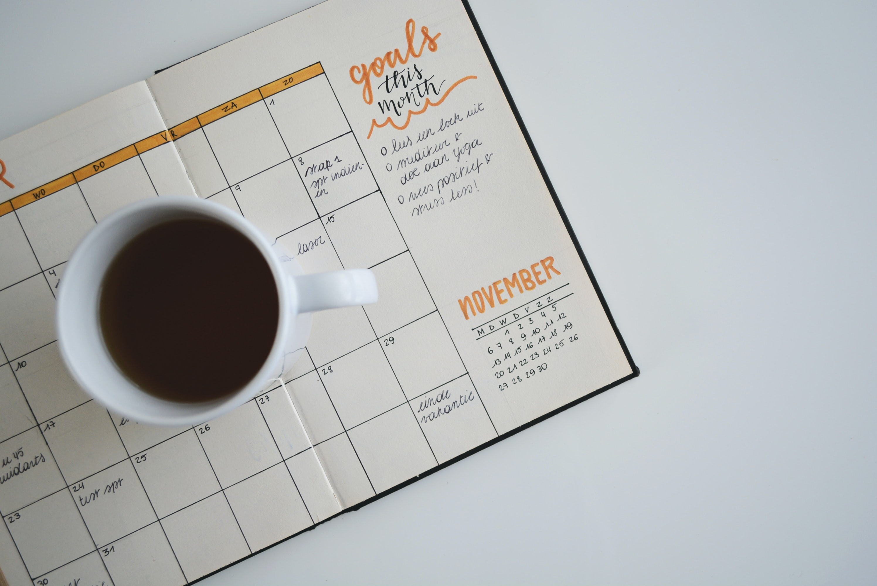 Coffee cup sitting on an open paper planner