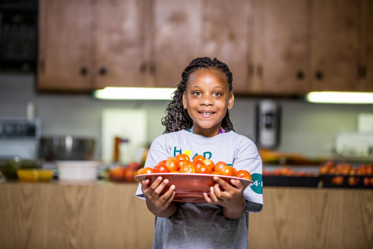 Young person holding plate of tomatoes