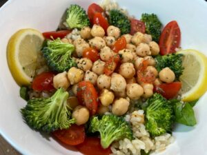 bowl filled with tomatoes, broccoli, chickpeas, rice, and garnished with lemon